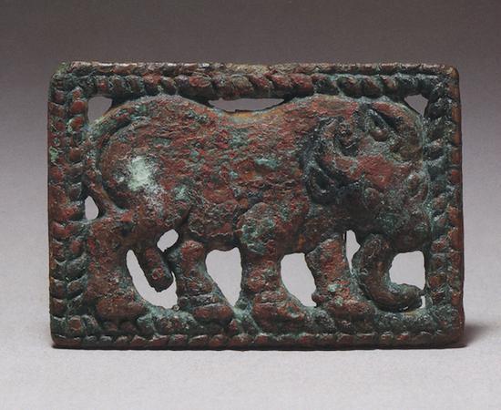 1983年在宁夏同心倒墩子匈奴墓出土的牛纹牌饰(图13)