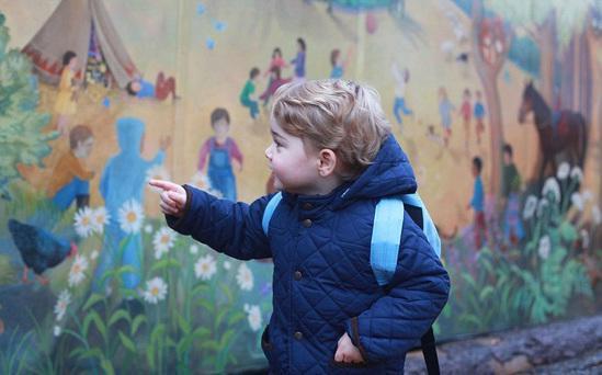 2岁半的乔治身穿有套头帽的深蓝棉夹克,背着浅蓝背包,站在学校彩色壁画前,他在看壁画。