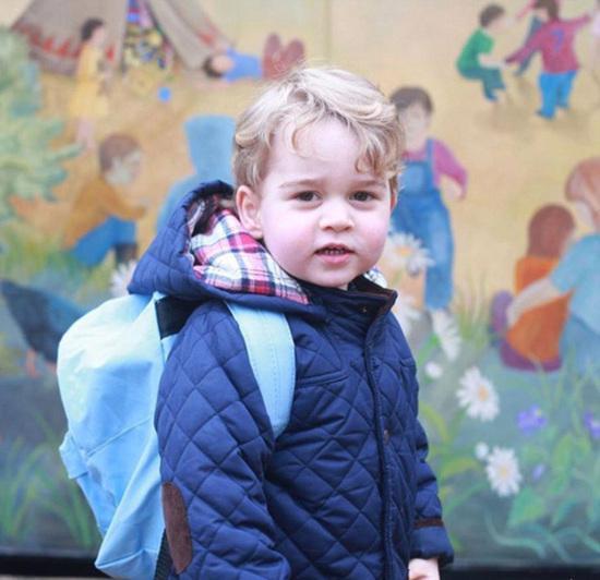 2岁半的乔治身穿有套头帽的深蓝棉夹克,背着浅蓝背包,站在学校彩色壁画前。