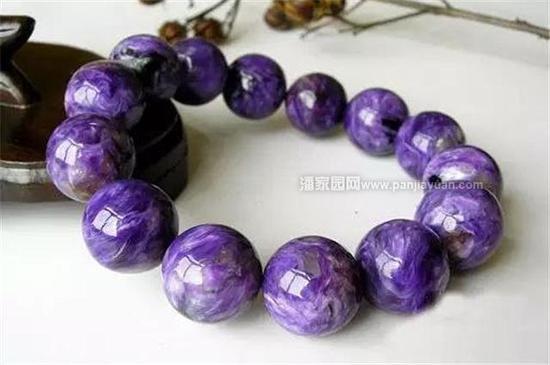 """紫龙晶是1978年才在前苏联雪利河畔发现的罕见稀有的紫色宝石,是由含强碱性的霞石正长岩入侵到石灰岩中由于特殊的压力、温度、化学成份、物理条件所构成的转变,形成了世界独一无二的""""紫龙晶""""。紫龙晶颜色鲜艳,紫白相间,以紫为主,紫色、白色成细长纤状无定向缠绕""""扭""""在一起,极似烧料,还有少量深绿色的斑块局部分布,长纤状互相缠绕,似众龙云飞舞,故称紫龙晶。颜色纯正、深紫的紫龙晶,价格也在飞涨,是新锐宝石中的潜力股。"""