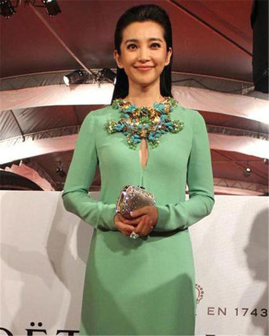 一袭苹果绿长袖礼服,搭配由玉、黄水晶和绿松石组成项链装饰,映衬出白皙精致的妆容,优雅大气又不失庄重。