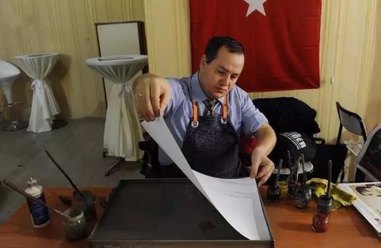 土耳其湿拓画的大师在小心翼翼地铺纸