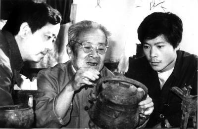 师父赵振茂(中)给王有亮(右)讲述青铜器细节