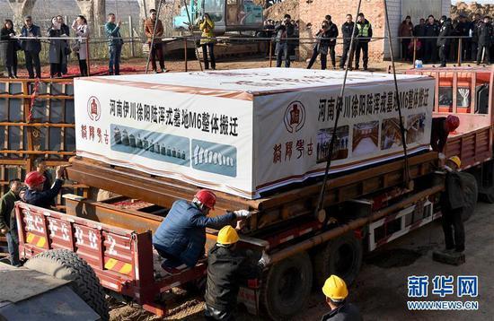 12月8日,在洛阳市伊川县徐阳村,工作人员利用大型机械将包裹着墓葬的木箱移至大货车上。新华社记者 李安 摄