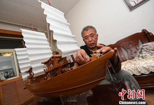 """68岁的闫嘉义是山西太原一名退休职工,尽管居住在内陆省份,他却对船非常感兴趣,亲手制作过不少大大小小的船只。12月21日,他拿出最满意的作品向记者展示,并将其命名为""""嘉义号""""。 武俊杰 摄"""