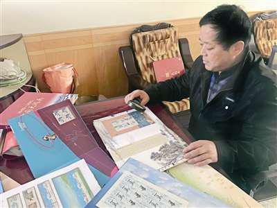 王明网正在翻看自己收集的邮票。(赵尉童/摄)