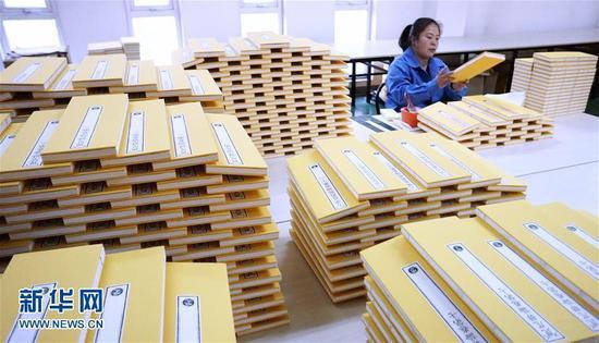 1月6日,技术人员在装订《清敕修大藏经》。