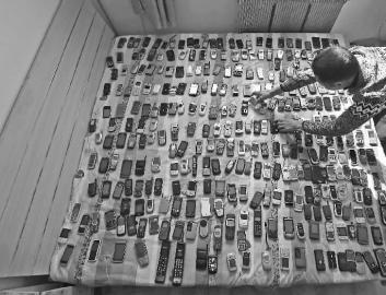 铺满一床的手机只是李清林藏品的一小部分