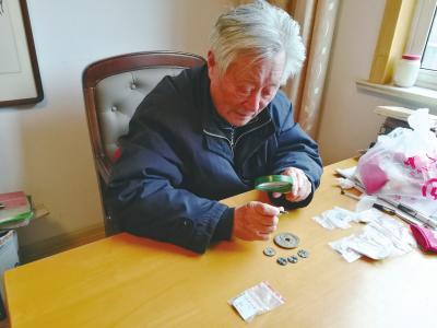图为曾闵正在认真研究自己收藏的古钱币。