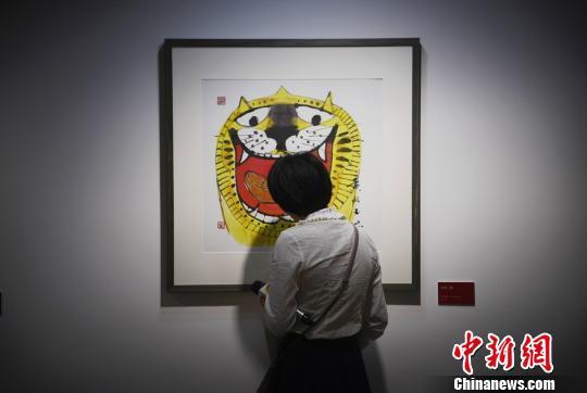 一位记者观看黄永玉的生肖画老虎。 杨华峰 摄