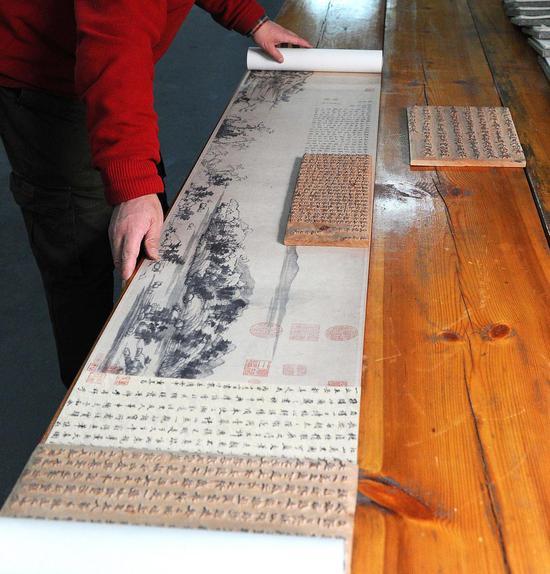 魏立中正在查看木刻水印的富春山居图。