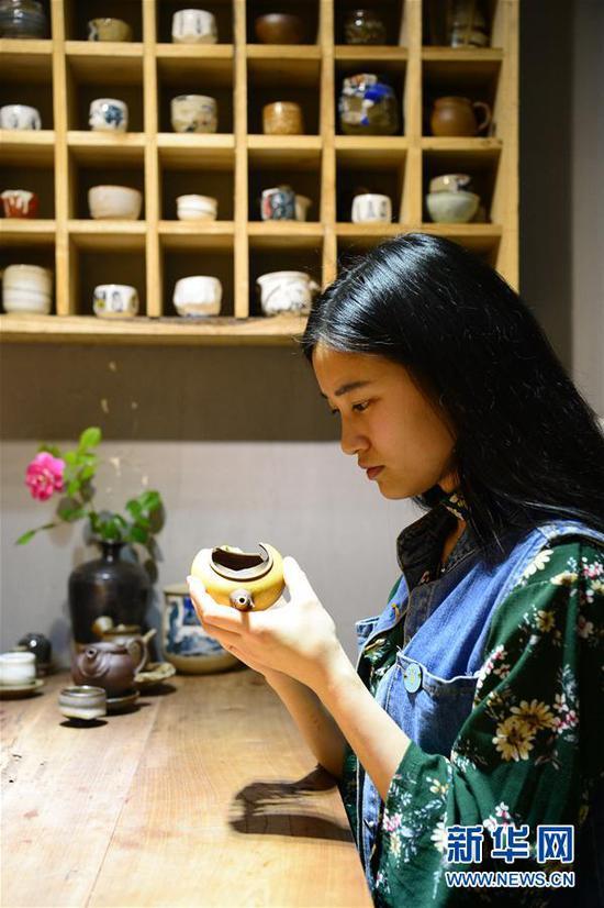 5月5日,黄俊玲在陶坊店面内查看一把破损的茶壶。