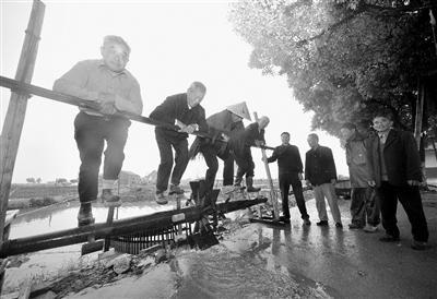 几位老人在演示踩水车