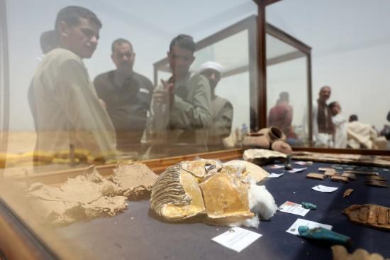 5月13日,在埃及中部明亚省,人们观看出土的文物。