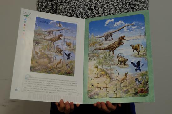 工作人员展示《恐龙世界》邮票拼图卡书