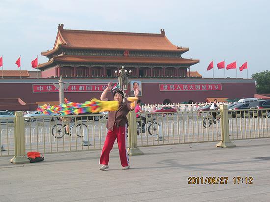 7、一名抖空竹的老人从外地来到北京,在天安门广场表演抖空竹作为留念。