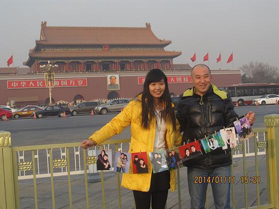 19、一对年轻夫妇带着记录他们恋爱过程的照片来到天安门前,高源看到后,主动给他们拍照留念。