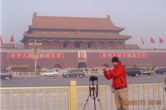 14、一名外国游客在天安门前手拿地球仪进行自拍,并指着地球仪上的中国地理位置。