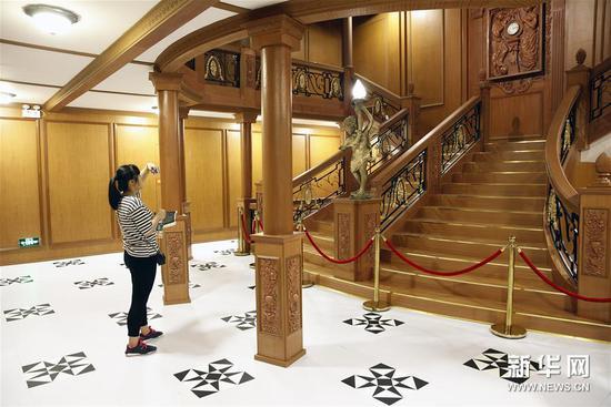6月16日,一名观众在泰坦尼克号的豪华楼梯再现场景中拍照。