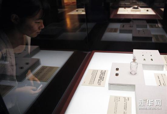 """6月16日,一名观众在欣赏""""泰坦尼克文物精品展""""展出的部分首饰。"""