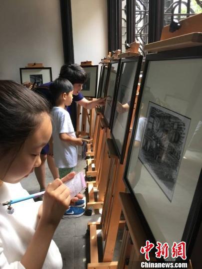"""6月18日,一场题为""""老街的记忆""""钢笔画展在江苏周庄古镇博物馆开展,100余幅钢笔画以独特线条和黑白色调再现江南老街风姿。图为游人观展。 黄莹 摄"""