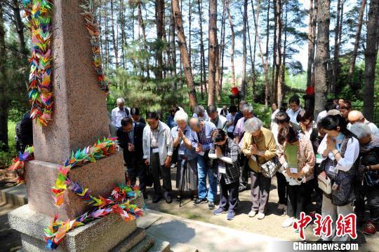 """日本遗孤代表在""""中国养父母公墓""""墓碑前祭拜 王舒 摄"""