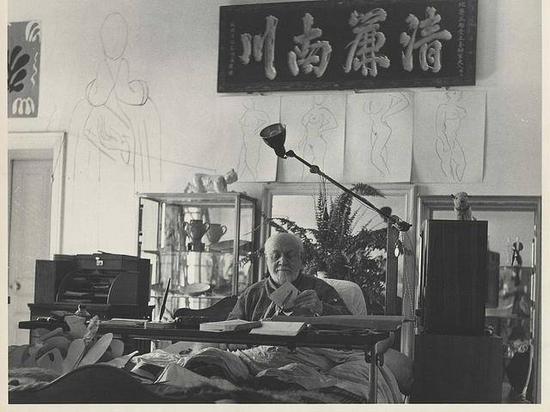 1951年3月,马蒂斯在工作室中一件中国书法作品下创作剪纸作品。摄影:Philippe Halsman (图片来源于网络)