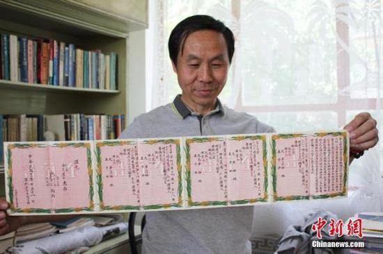 """图为近日,在位于甘肃临洮县的家中,收藏""""达人""""杨楠展示民国时期的金兰谱。徐雪摄"""