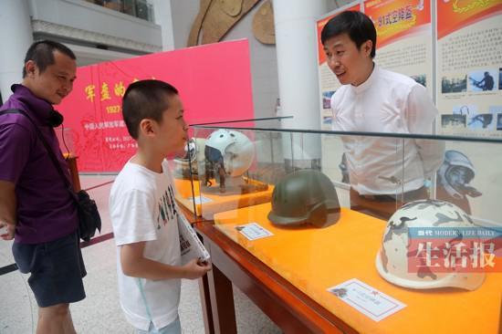 农健在给小朋友讲解军用头盔的知识