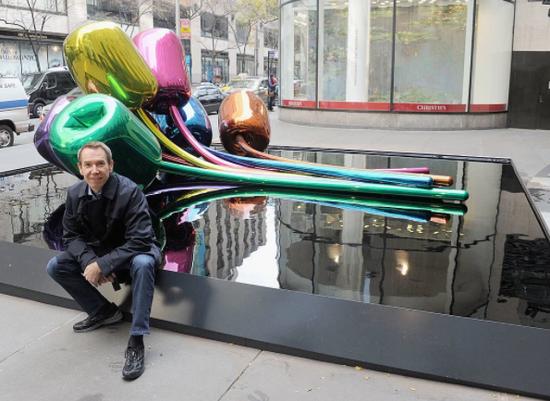 杰夫·昆斯在他的雕塑《郁金香》前拍照,该作品与赠送给巴黎市的礼物的设计类似。图片:Jamie McCarthy / Getty Images