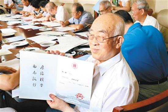 老教授文占申展示精心书写的录取通知书。图片来源于:西安晚报
