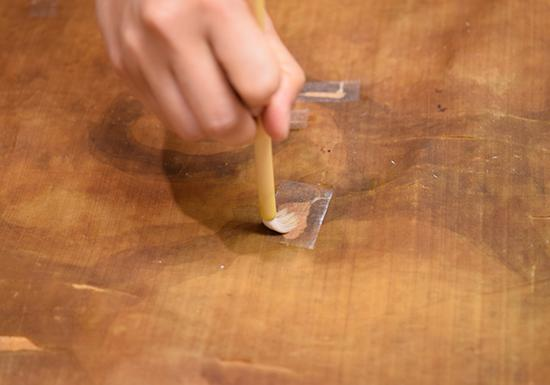 背面经过清洗后,在粘胶纸条上涂上日本海萝胶(funori),用来稳定破损和撕裂的区域。