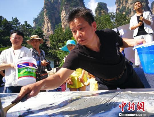 23日,李军声在张家界武陵源现场创作砂石画百米长卷。 王建军 摄