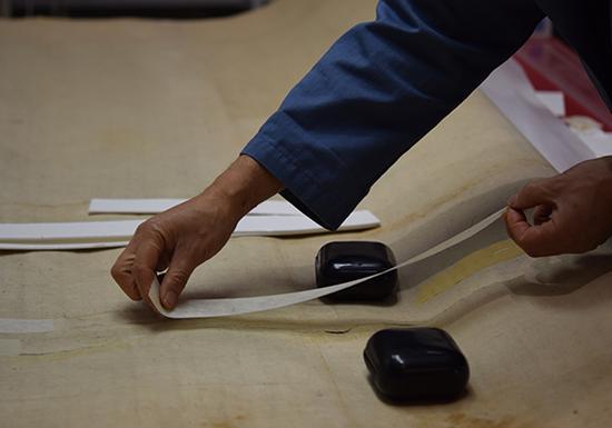 修复师将手工纸放在有撕裂处的背面,并糊上小麦淀粉