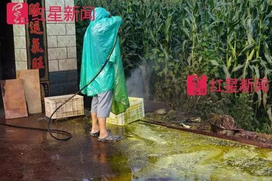 一个穿着雨披冲洗麻核桃的人