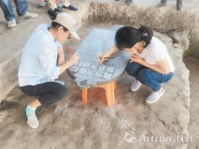 图说:考古人员在整理墓志铭 官方图