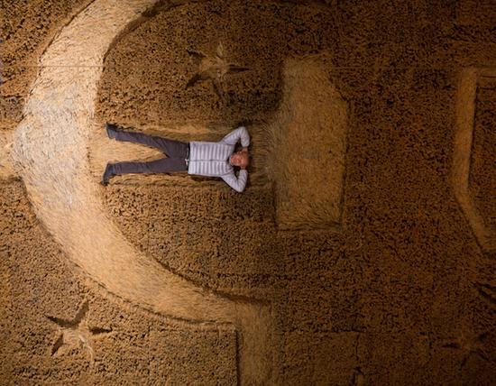 蔡国强躺于作品《大地》中,普希金国家艺术博物馆,莫斯科,2017年。赵小意摄,蔡工作室提供