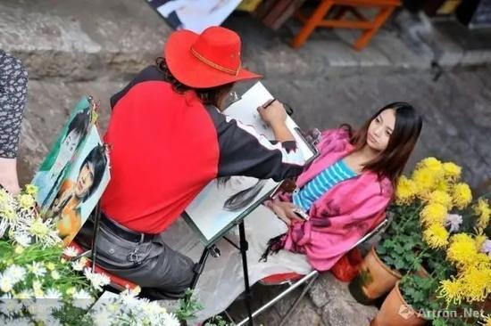 街头一江湖画家正在为一女子画像 图片来源于网络