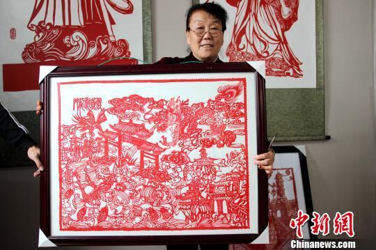 图为赵文花展示其剪纸作品《鲤鱼跃龙门》。 阿琳娜 摄