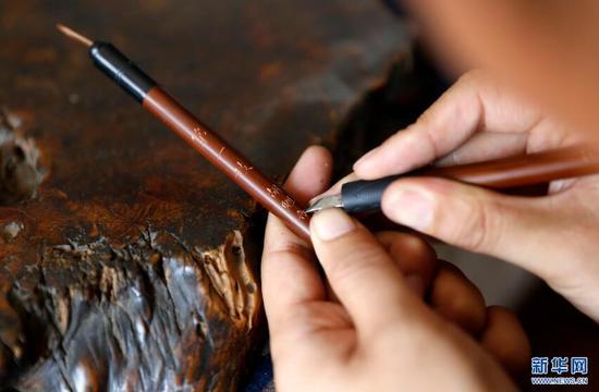 9月20日,张忠新师傅在制作好的毛笔上课上字。 新华网 姜冰摄