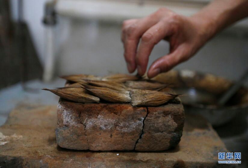 9月20日,李世美将笔毛放在烧热的砖头上熥。 新华网 姜冰摄