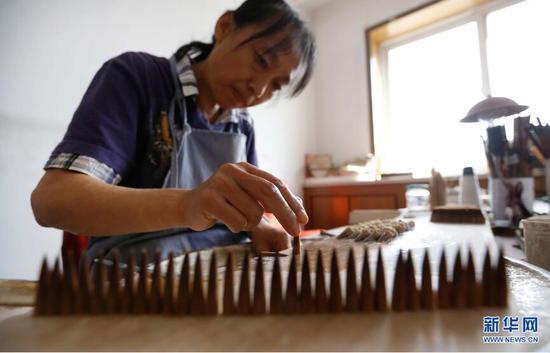 """9月19日,李世美在进行毛笔加工的""""水盆""""工序。 新华网姜冰摄"""