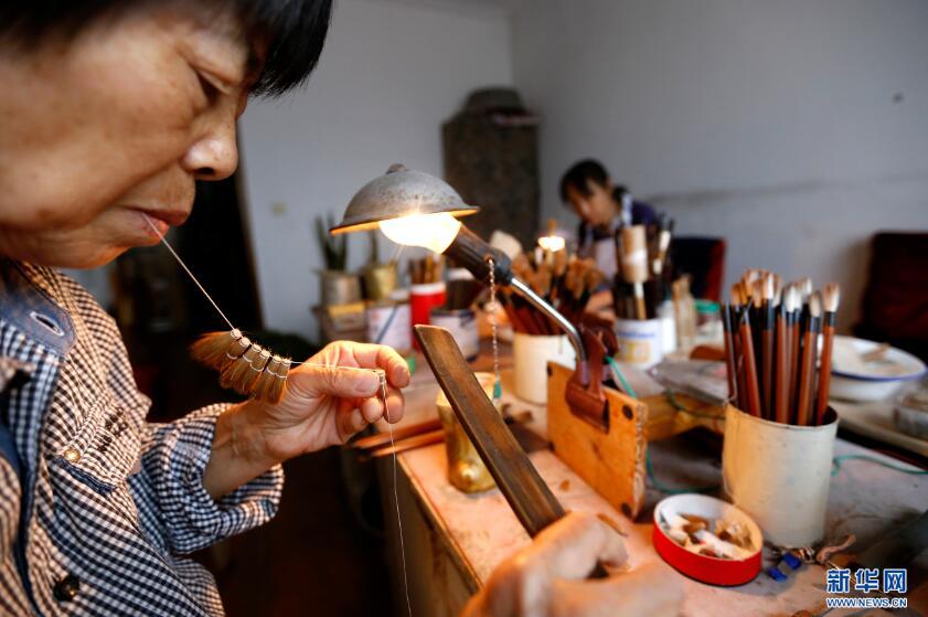 9月19日,张国茹(左)将毛笔头用绳子穿起准备晾晒。新华网 姜冰摄