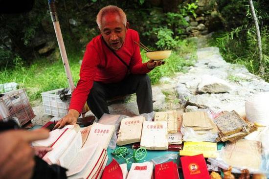 在河南太行山大峡谷景区内,路遇一位摆地摊的老人在出售当地特产及一些古董书及粮票,让许多上了年岁的人看后来了兴趣。