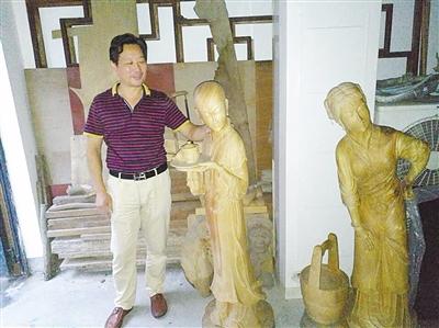 胡建能和他的圆雕作品。(徐欣摄)
