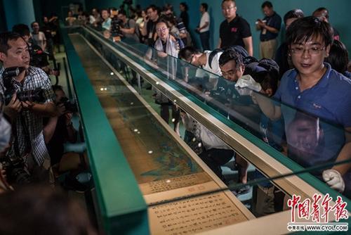 9月11日,北京故宫午门正殿,《千里江山——历代青绿山水画特展》媒体专场,工作人员展开北宋王希孟的《千里江山图》画卷。北京故宫博物院2017年的年度大展《千里江山——历代青绿山水画特展》以《千里江山图》为中心系统梳理、展示中国历代青绿山水画的发展脉络,于9月15日