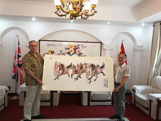 图 黄俊杰先生在金丝路联盟北京总部向英国皇家易思男爵教授赠送《丝路·八骏图》