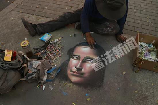 """法制晚报2017年9月12日报道,记者在北京三里屯附近,看到了正在用粉笔作画的""""流浪艺术家""""曾祥绿。"""