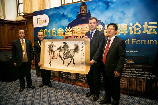 图 黄俊杰先生(左二)向英国贸易与投资部长格莱格·汉斯先生赠送亲笔作品《双骏》,象征中英黄金时代的友好合作