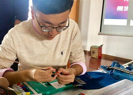 """胡睿杰正在为自己的参赛作品""""牛仔收纳袋""""收尾。 澎湃新闻记者 胡芮默 图"""